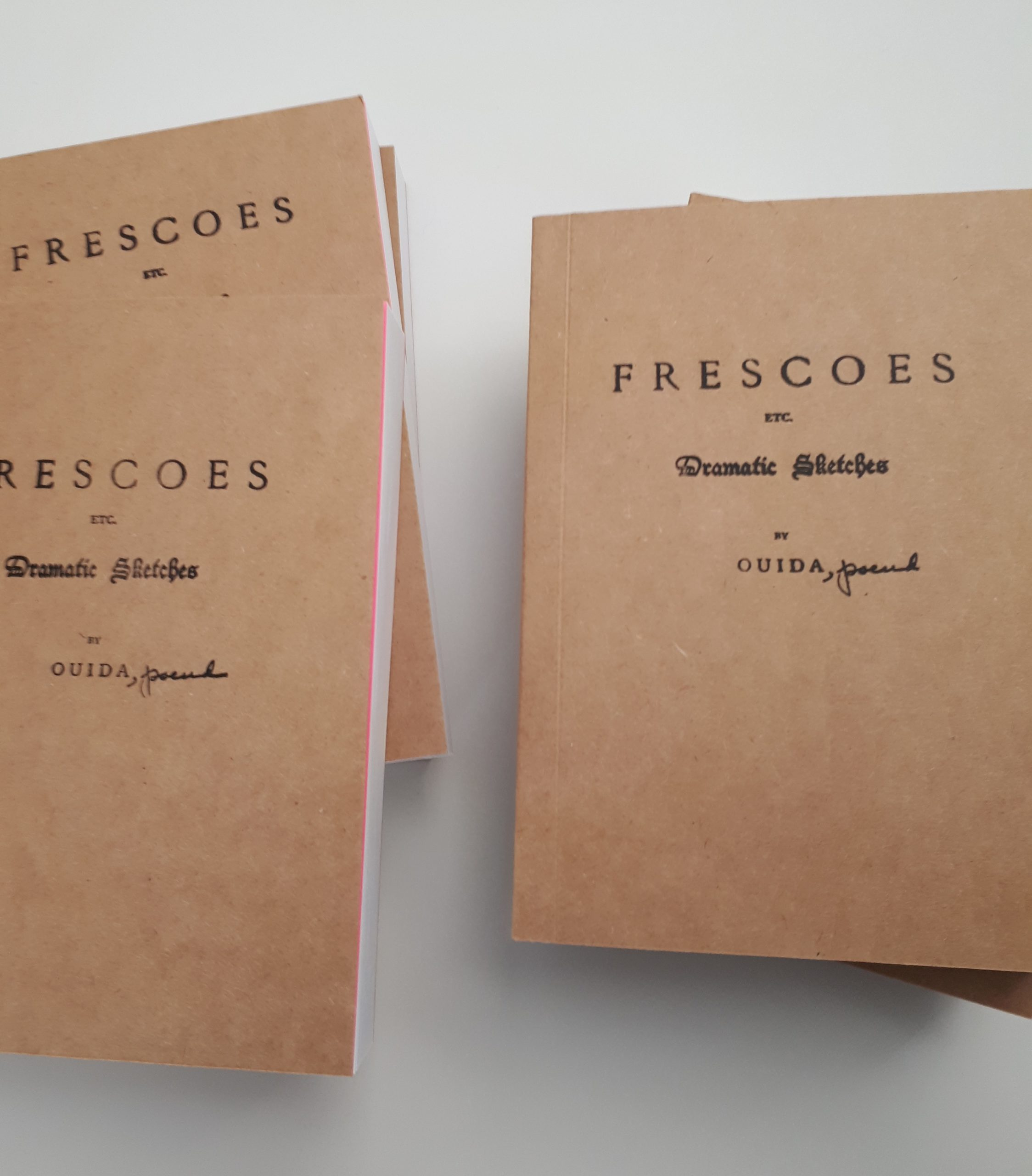"books with covers made of rough chipboard paper, showing cover title ""FRESCOES etc. Dramatic Sketched by OUIDA"" with the work ""pseud."" written in cursive next to the name ""OUDIA"". On one of the books can be seen a glimpse of a vibrant pink paper inside the front cover before the book's actual pages."