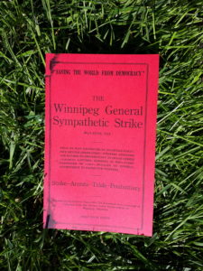 """A book with bright read covers laying on a surface of vibrant green grass. The cover reads in part """"'Saving the World from Democracy', The Winnipeg General Sympathetic Strike"""""""