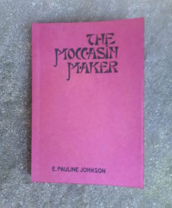 """A book with burgundy-coloured cover, titled """"The Moccasin Maker"""" by author E. Pauline Johnson, laying on a mottled stone surface"""