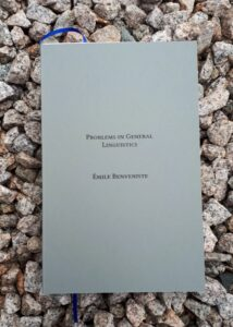 """A book with a slate gray cover and blue marker ribbon lies on a bed of sharp gravel. Text on the cover reads """"Problems in General Linguistics, Emile Benveniste"""""""